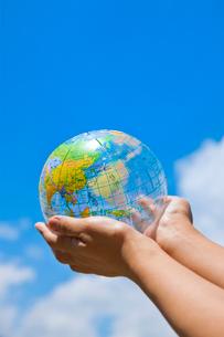 青空をバックに透明な地球儀を持つ女性の手の写真素材 [FYI02356696]