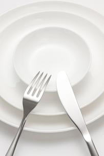 白バックのナイフとフォークと白い皿の写真素材 [FYI02357581]