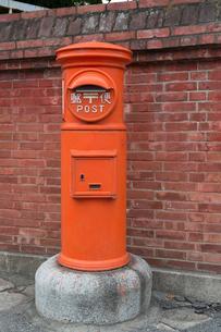 赤い郵便ポストとレンガの塀の写真素材 [FYI02358147]