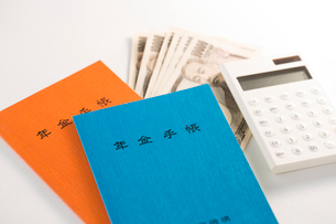 年金手帳と紙幣、電卓の写真素材 [FYI02358956]