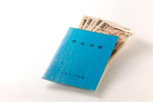 年金手帳と紙幣の写真素材 [FYI02359074]