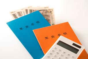 年金手帳と紙幣、電卓の写真素材 [FYI02359341]