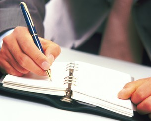 手帳に記入する男性の写真素材 [FYI02380359]