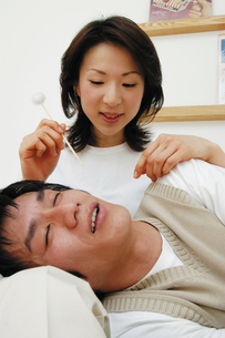 耳かきをする女性と横になる男性の写真素材 [FYI02388669]