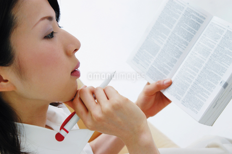 辞書とペンを持つ女性の写真素材 [FYI02391707]