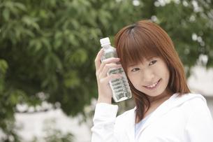 ペットボトルを顔に当てる女性の写真素材 [FYI02398762]