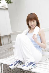 ベンチで両足を組み休む女性の写真素材 [FYI02398828]
