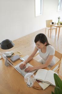 部屋でパソコンを使う女性の写真素材 [FYI02399190]