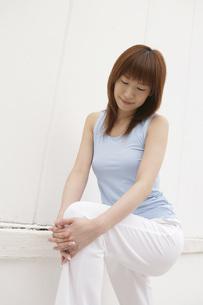膝を抱えて足を伸ばす女性の写真素材 [FYI02399400]