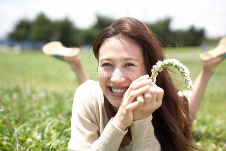 草むらに寝転ぶ女性の写真素材 [FYI02399506]