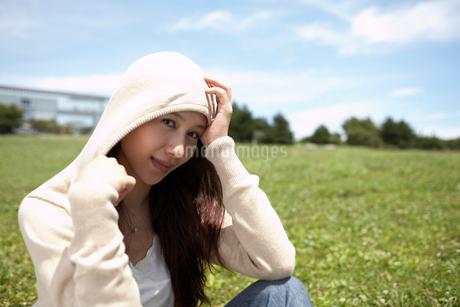 草むらに座る帽子をかぶった女性の写真素材 [FYI02399796]