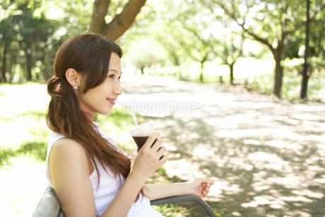 公園のベンチに座る女性の写真素材 [FYI02399957]