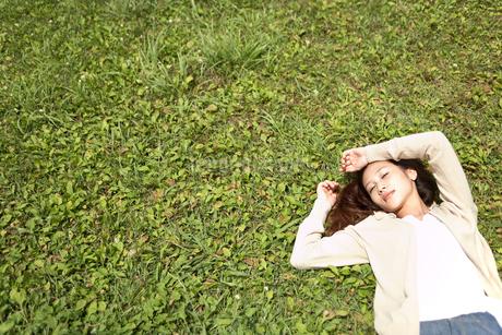 草むらに寝転ぶ女性の写真素材 [FYI02400024]