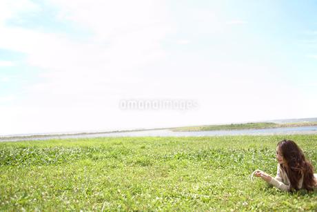 草むらに寝転ぶ女性の写真素材 [FYI02400051]