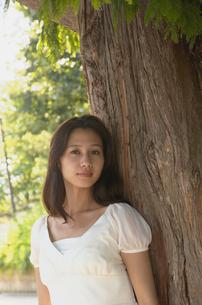 木に寄りかかる女性の写真素材 [FYI02400056]