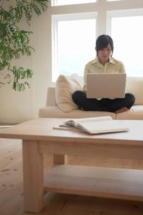 ソファに座り、パソコンを使う女性の写真素材 [FYI02400074]