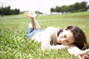 草むらに寝転ぶ女性の写真素材 [FYI02400079]