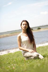 草むらに座る女性の写真素材 [FYI02400081]