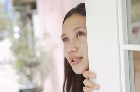 扉から顔を出す女性の写真素材 [FYI02400085]