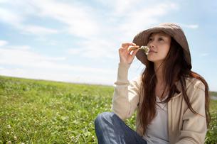 花の匂いをかぐ帽子をかぶった女性の写真素材 [FYI02400093]