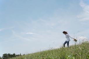 草むらを歩く女性の写真素材 [FYI02400097]