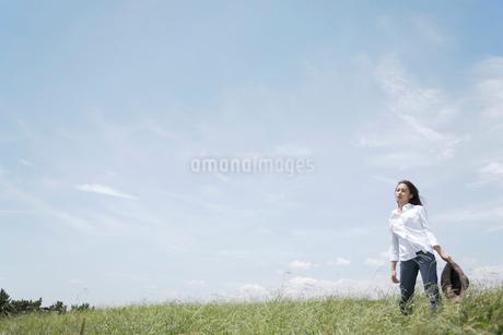 草むらにたたずむ女性の写真素材 [FYI02400108]