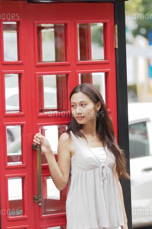 扉に寄りかかる女性の写真素材 [FYI02400266]