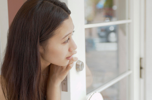 扉から顔を出す女性の写真素材 [FYI02400326]