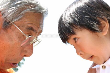 にらめっこをするシニア男性と子どもの写真素材 [FYI02400485]