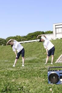 土手で体操する2人の少女の写真素材 [FYI02400489]