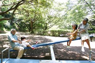 シーソーで孫と遊ぶ祖父母の写真素材 [FYI02400750]