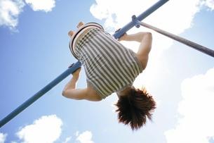 鉄棒をする男性と青空の写真素材 [FYI02401104]
