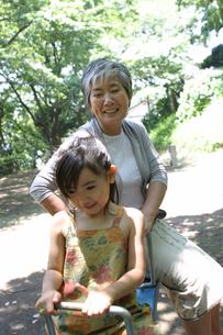 シーソーで孫と遊ぶ祖母の写真素材 [FYI02401143]