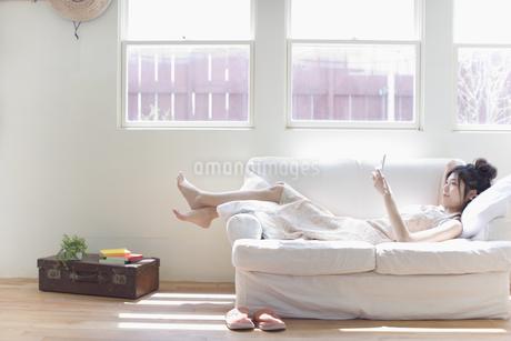 ソファに寝そべる女性の写真素材 [FYI02401512]