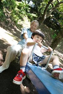 シーソーで孫と遊ぶ祖父の写真素材 [FYI02401601]