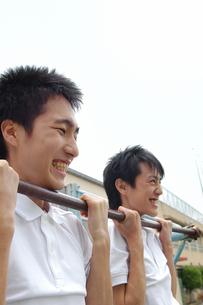 鉄棒にぶら下がる男子生徒2人の写真素材 [FYI02401775]