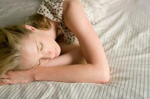 ベッドで横になる女性の写真素材 [FYI02401847]