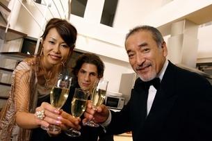 シャンパンを持った女性と2人の男性の写真素材 [FYI02401894]
