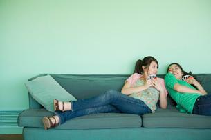 ソファーに寝転がる女性の写真素材 [FYI02402456]