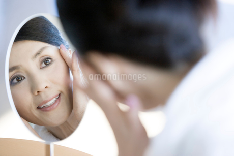 鏡を見る女性の写真素材 [FYI02403049]