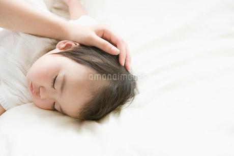 眠っている赤ちゃんを撫でるお母さんの手の写真素材 [FYI02403135]