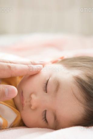 眠っている赤ちゃんとお父さんの手の写真素材 [FYI02403346]