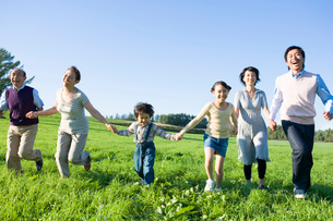 草原を走る家族の写真素材 [FYI02403721]
