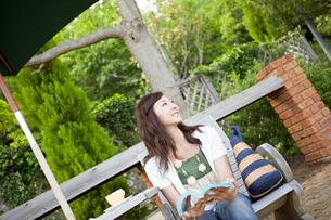 デッキチェアに座って遠くを見る女性の写真素材 [FYI02406854]