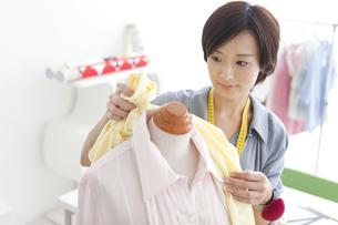トルソーに布をあてるパタンナーの女性の写真素材 [FYI02406941]