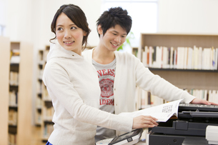 コピー機の前で本を開くカップルの写真素材 [FYI02408132]