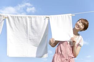 洗濯物を干す若い女性の写真素材 [FYI02408419]