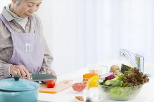 トマトを切る中高年女性の写真素材 [FYI02408843]