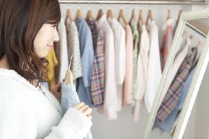 鏡の前で洋服を選ぶ女性の写真素材 [FYI02409269]