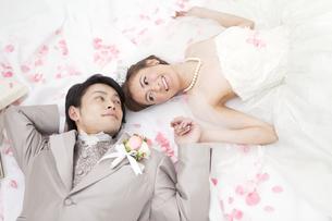 寝転ぶ新郎新婦と花びらの写真素材 [FYI02409376]